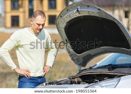 unhappy man looking at broken car - stock photo