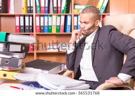 unhappy man looking at stack of folders - stock photo