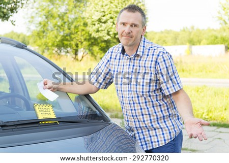 unhappy man looking on parking ticket placed under windshield wiper - stock photo