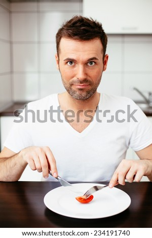 Unhappy man on diet cutting a piece of tomato - stock photo
