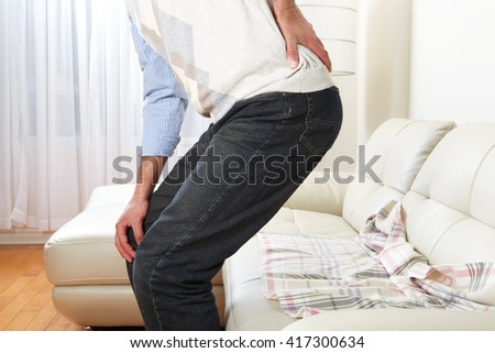 Unhappy man suffering from backache at home - stock photo