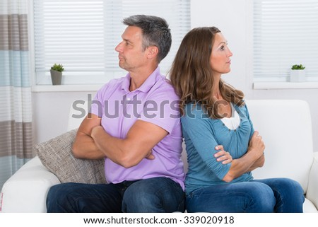 Unhappy Mature Couple With Armcrossed Sitting On Sofa After Quarrel - stock photo