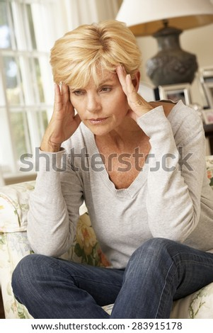 Unhappy Mature Woman Sitting On Sofa At Home - stock photo