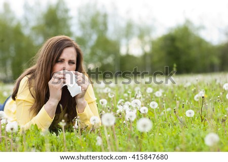 Unhappy middle age woman with hay fever and handkerchief lying in the grass