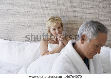Unhappy middle aged couple in bedroom - stock photo