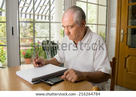 Unhappy old man calculating the monthly expenses at home - stock photo