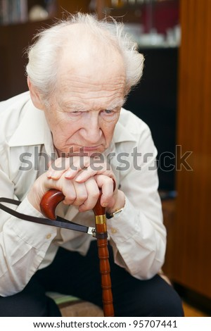 unhappy old man holding his cane - stock photo