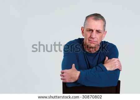 unhappy older man seated looking down