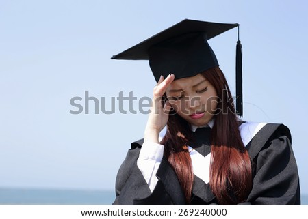 unhappy sad student woman graduating with sky background, asian beauty - stock photo