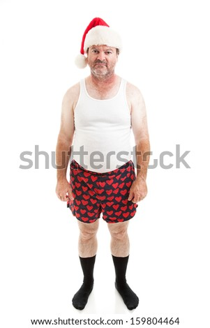 Unhappy, scruffy looking middle-aged man in his underwear, wearing a Santa hat for Christmas and looking upset.  Isolated on white.   - stock photo