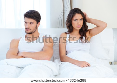 Unhappy separate couple lying in a bed at home - stock photo