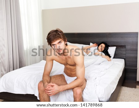 unhappy separate couple lying in a bed, having conflict problem cheat, upset man sad negative emotions concept - stock photo