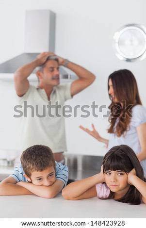 Unhappy siblings sitting in kitchen with their parents who are arguing loudly at home - stock photo