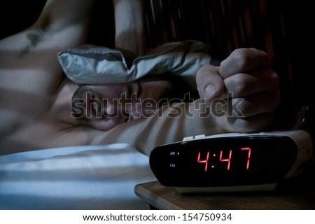 Unhappy sleeping man smashing the alarm clock in the morning (very early). - stock photo