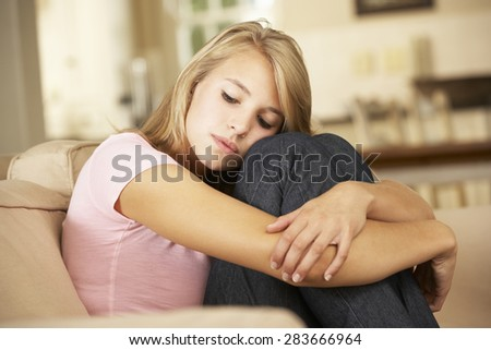 Unhappy Teenage Girl Sitting On Sofa At Home - stock photo