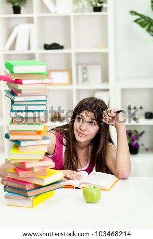 Unhappy teenage girl with big stack of books - stock photo