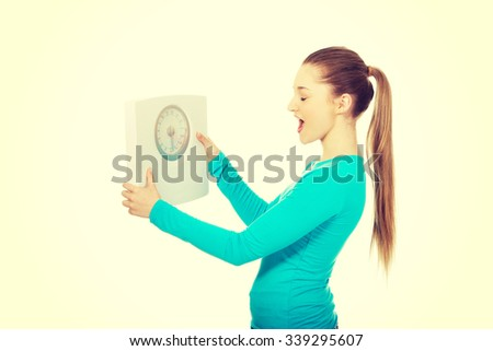 Unhappy teenage woman holding scale.