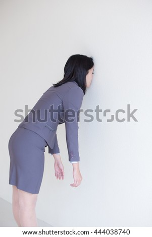 Unhappy thinking business woman with white wall background, great for your design or text, asian