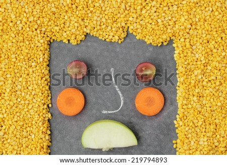 Unhappy vegetables face on black background.
