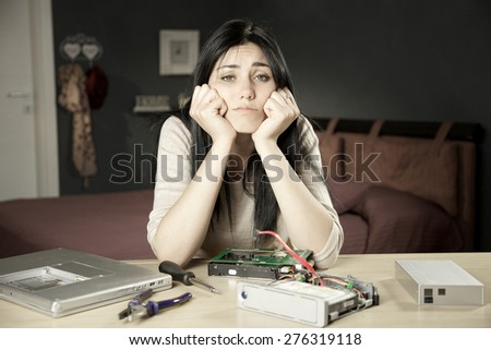 Unhappy woman at home with broken technology - stock photo