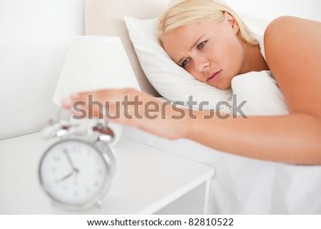 Unhappy woman awaken by an alarm clock in her bedroom - stock photo