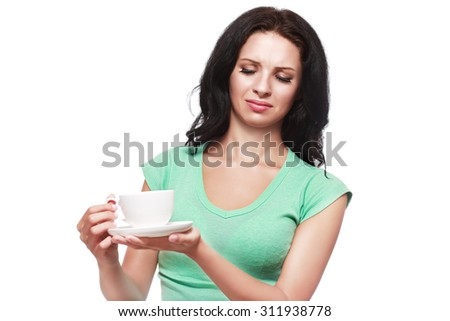 unhappy woman doesn't like her drink coffee or tea and looking at it looking scared or disgusted