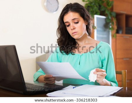 Unhappy woman looking documents with laptop at table