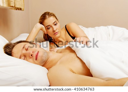 Unhappy woman lying in bed stressed when her husband sleeping