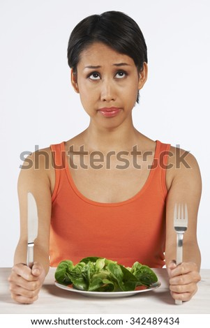 Unhappy Woman Sitting In Front Of Lettuce Leaves On Plate - stock photo