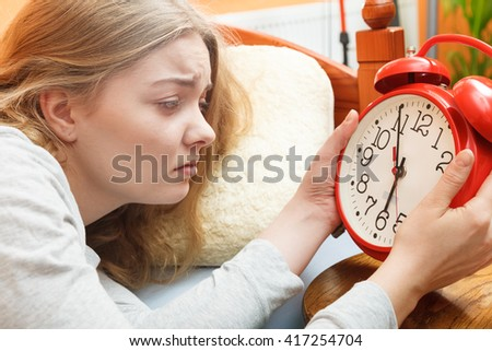 Unhappy woman waking up in bed turning off alarm clock. Young girl in the morning.