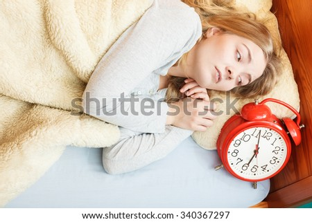 Unhappy woman waking up in bed with alarm clock. Young girl in the morning.