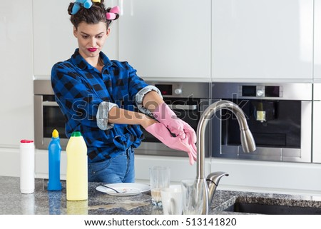 Unhappy woman with a hair rollers cleaning big kitchen