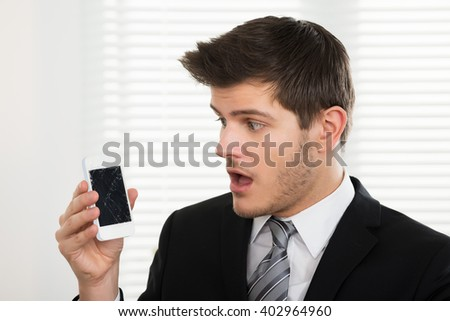 Unhappy Young Businessman Looking At Broken Mobile Phone In Office - stock photo