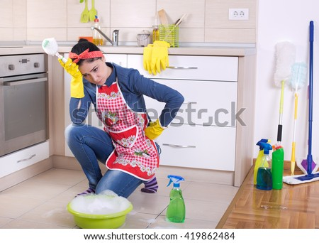 Unhappy young cleaning lady holding head with hand and squatting in front of cleaning supplies and equipment - stock photo