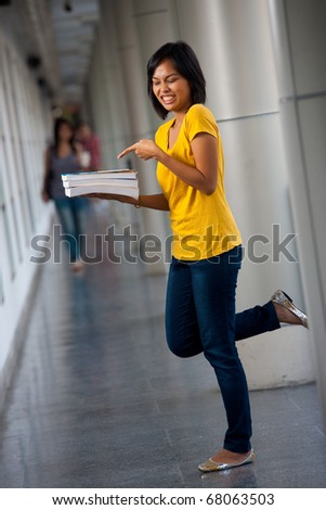 Unhappy young college student in yellow shirt holding, pointing at her textbooks with a disgusted expression balancing on one leg. Twenties female Asian Thai model of Chinese descent looking away