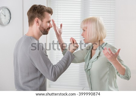 Unhappy Young Couple Arguing With Each Other At Home - stock photo