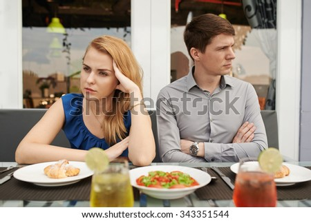 Unhappy young couple sitting in the restaurant - stock photo