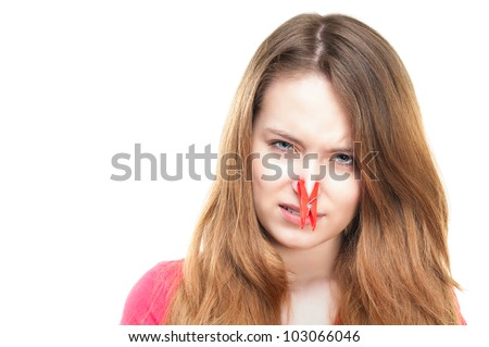 Unhappy young girl feeling bad smell. Disgusted expression, red clothespin on her nose. Looking into the camera. Isolated on white background.