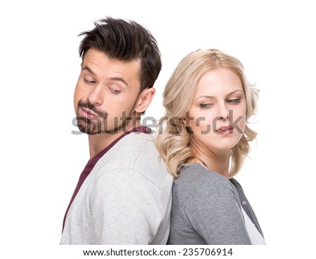 Unhappy young man and woman are standing back each other and not speaking, isolated on white background. - stock photo