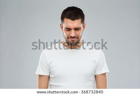 unhappy young man over gray background - stock photo