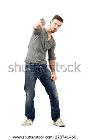 Unhappy young man showing thumbs down gesture.  Full body length isolated over white background. - stock photo