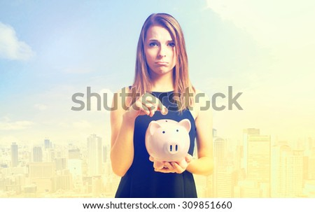 Unhappy young woman depositing money into her pink piggy bank  - stock photo