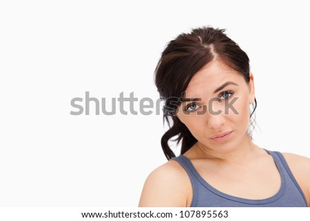 Unhappy young woman looking at camera against white background