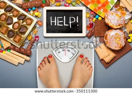 Unhealthy diet - overweight. Feet on bathroom scale and chocolate, jelly cubes, candies, chocolate bars, cookies, donuts - stock photo