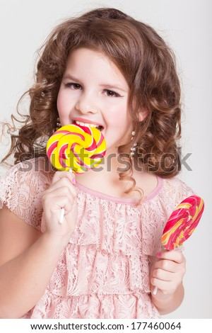 Unhealthy eating - funny child with big candy lollipop, happy little girl eating big sugar lollipop, kid eat sweets. surprised child with candy. isolated on white background, studio. - stock photo