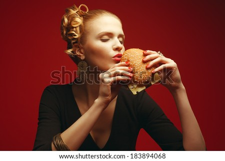 Unhealthy eating. Junk food concept. Guilty pleasure. Fashionable hipster girl holding & eating cheeseburger over red background. Perfect hair, skin, make-up & manicure. Copy-space. Studio shot - stock photo