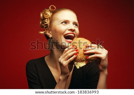 Unhealthy eating. Junk food concept. Guilty pleasure. Happy fashionable hipster girl holding & eating cheeseburger over red background. Perfect hair, skin, make-up & manicure. Copy-space. Studio shot