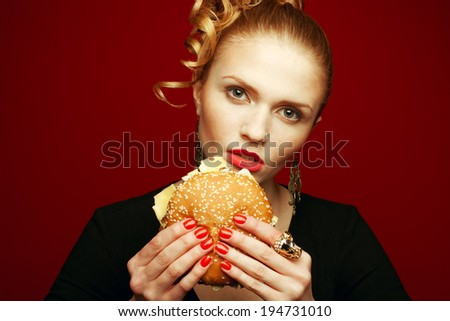Unhealthy eating. Junk food concept. Guilty pleasure. Happy fashionable model holding burger & eating over red background. Perfect hair, skin, make-up & manicure. Copy-space. Close up. Studio shot - stock photo