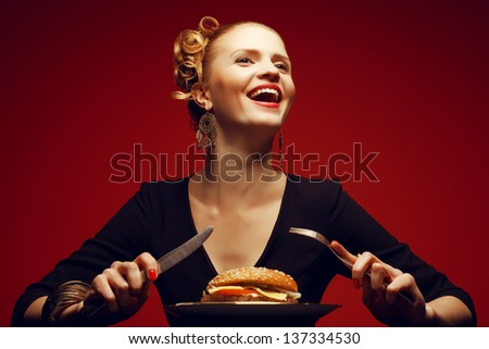 Unhealthy eating. Junk food concept. Portrait of a happy fashionable young woman holding fork and knife and going to eat burger. Perfect hair, skin, make-up and manicure. Copy-space. Studio shot - stock photo