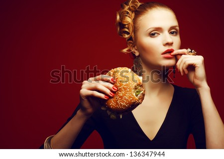 Unhealthy eating. Junk food concept. Portrait of fashionable young woman holding burger and posing over red background. Copy-space. Perfect hair, skin, make-up and manicure. Studio shot - stock photo